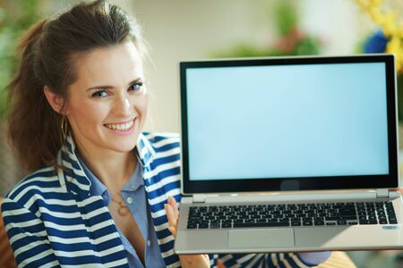 Photo pour happy modern 40 years old woman in blue blouse and striped jacket at modern home in sunny day sitting on couch and showing laptop blank screen. - image libre de droit