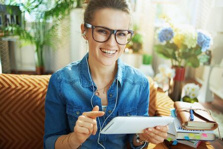 Photo pour Portrait of smiling modern 40 years old woman in jeans shirt with white headphones and tablet PC study online in the modern house in sunny day. - image libre de droit
