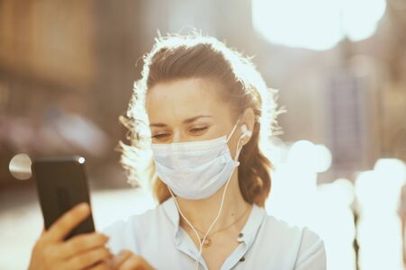 Photo pour Life during coronavirus pandemic. 40 years old woman in blue blouse with medical mask having virtual meeting outdoors on the city street. - image libre de droit