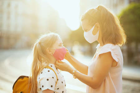Photo pour Life during covid-19 pandemic. young mother and child with masks and yellow backpack getting ready for school outside. - image libre de droit