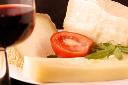 Plate with pecorino, parmesan and emmenthal cheese with a half tomato, rocket and a glass of red wine