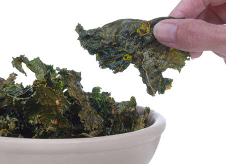 Kale chips in a bowl with a hand holding one.  Isolated on white.