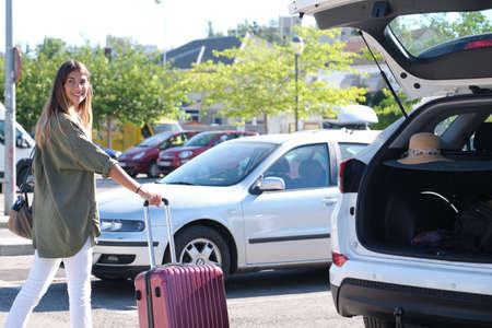 Photo pour Young woman getting her suitcase out from the luggage boot of the car. Holidays concept. - image libre de droit