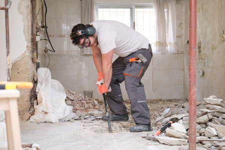 Photo pour Builder digging up the house floor, lifting up old tiles with a crowbar. House renovation. - image libre de droit
