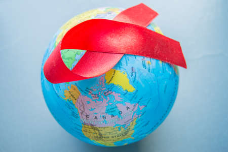Photo for World AIDS day 1 December, close-up of world globe with red ribbon - Royalty Free Image