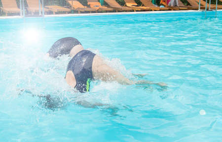 Photo pour Two female swimmers simultaneously dive in an outdoor pool, demonstrating their skill, Sunny summer day, light. - image libre de droit