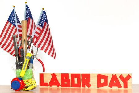 Foto de Bouquet of tools with US flags on a table and duct tape text on a board, concept of the patriotic holiday of labor day - Imagen libre de derechos