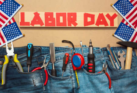 Foto de Jeans with tools on masonite plate with duct tape text and US flags, patriotic holiday concept of labor day, top view - Imagen libre de derechos