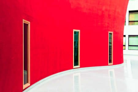 Photo pour Windows stand out Against waving a red wall and white floor inside a public building. - image libre de droit
