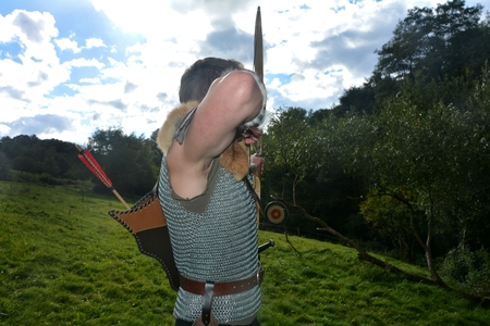 Young medieval archer from the back, aims with arrow and curve at straw disc in green nature