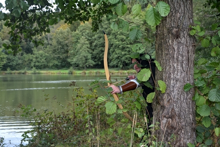 Medieval archer with black hood stands hidden behind tree in the lake with tense curve