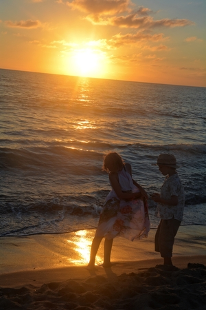 Girl and boy at the sundown on the beach