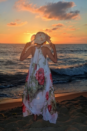 Girls in the long dress and holds with Both Hands care on the head and stands by the sea beach at the sundown, with look as the sun, the sun headcovers