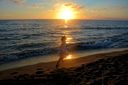 Girl in the long dress runs at the sundown along the beach