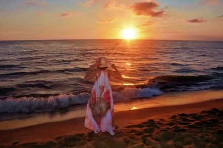 Girls in the long dress and holds with Both Hands care on the head and stands by the sea beach at the sundown, with look as the sun