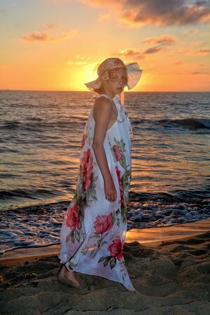 Girl in the long dress stands by the sea beach at the sundown, with look forwards and headcovers the sun