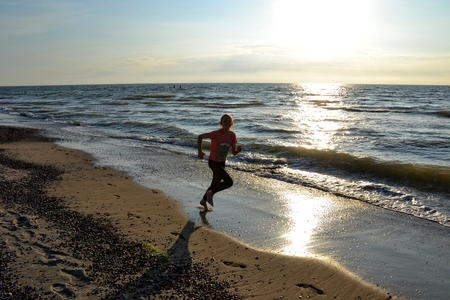 Girl runs at the sundown along the beach
