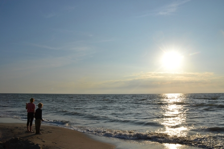 Two children stood at the sundown on the beach and look to the sea