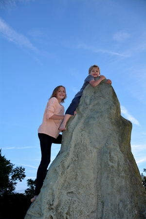 Two children with climb, boy holds on the point of a climb - rock, girl directly under him