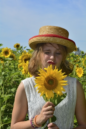 Girl with sunflower, makes funny face, stands in the sunflower field
