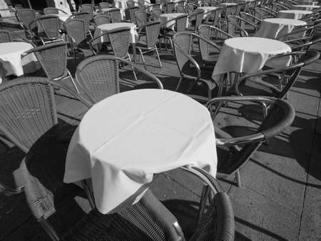 Many tables and chairs at an outdoor alfresco bar in black and white