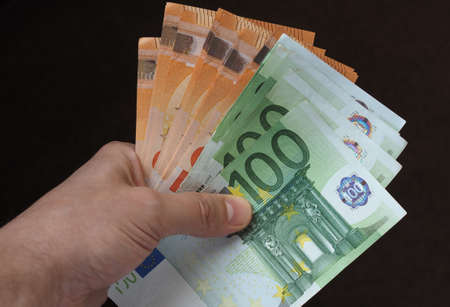 Photo pour Hand holding and giving Euro banknotes money (EUR), currency of European Union - image libre de droit