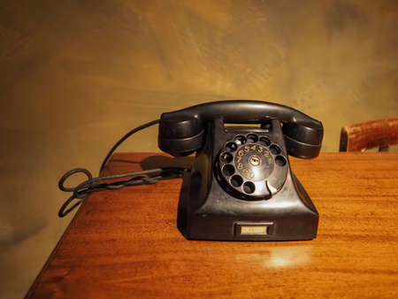 Photo for vintage black analog rotary dial telephone on a desk - Royalty Free Image