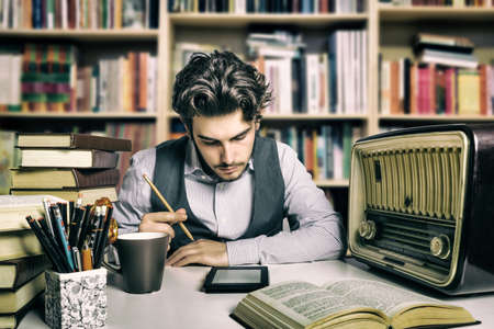 Foto per young adult reading an ebook over a desk full of books and various objects - Immagine Royalty Free