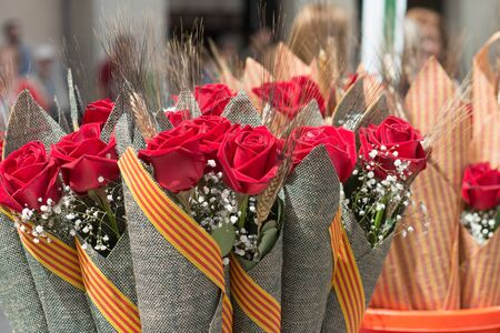 Barcelona, ??Spain_04 / 23/2018: typical bouquet of roses with Catalan flag of saint george day