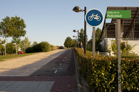 Happyness street plate in spanish and bike path.