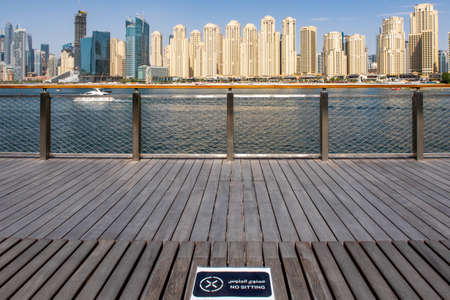 Dubai, UAE, 07/02/2020. View of wooden brown bench with NO SITTING sign in english and arabic due to COVID-19 safety precautions with Jumeirah Beach Residence (JBR) skyline and sea in the background.