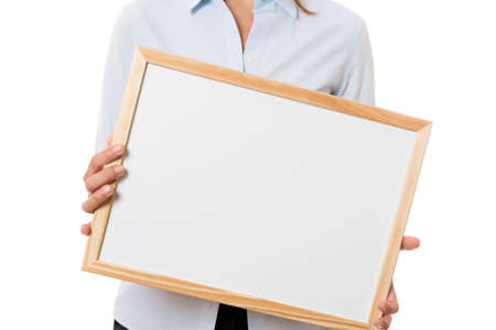 closeup of hands of a young business woman standing holding a whiteboard isolated on a white background - focus on the whiteboard
