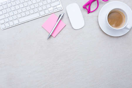 zenithal view of a business desk consisting on a a cup of coffee with a coffee saucer, wireless mouse, a keyboard, a pink eyeglasses and a pink sticky note with a pen on a beige desk background - suitable for copy space
