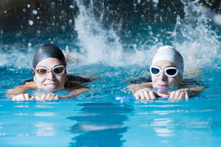 couple of female swimmers swimming with a swim board doing leg exercises in an indoor swimming pool - focus on the right woman face