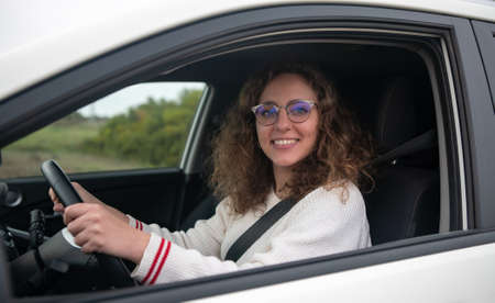 Photo pour Young woman smiling while holding the steering wheel of the car with her hands. The woman has curly blonde hair. New driver concept. - image libre de droit