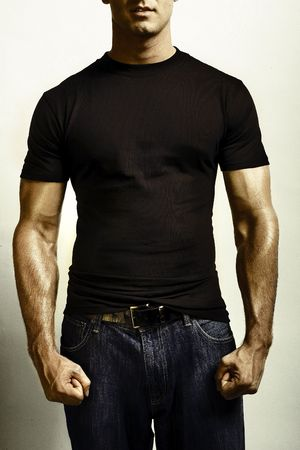 Photo pour A strong male adult flexing for camera in blank tshirt and jeans - image libre de droit