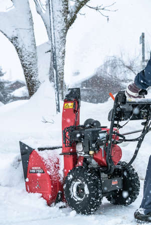 Photo pour A man cleans snow from sidewalks with snowblower in Bavaria Germany. - image libre de droit