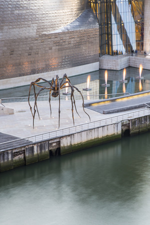 Bilbao, Spain - January 29, 2016: evening view of contemporary art Guggenheim Museum designed by American architect Frank Gehry and Maman, sculpture of a spider created by French artist Louise Bourgeois