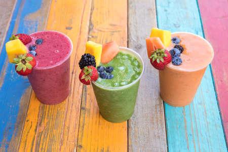 Foto de Colorful, tasty and healthy fruit smoothies on a colorful wood table - Imagen libre de derechos