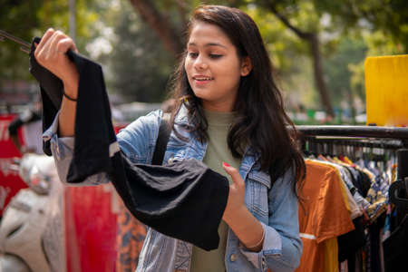 Photo pour Happy late teen girl looking and buying clothes from outdoor street market - image libre de droit