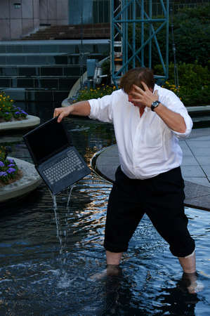 A laptop dropped into water by a businessman