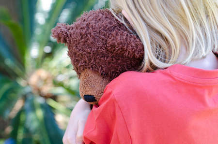 Little girl hugging her brown teddy close