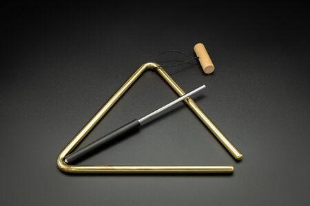 Photo pour Closeup of a brass triangle lying on a black underground - image libre de droit