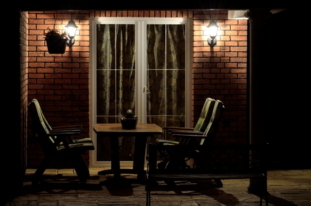 Modern house garden terrace (patio) lined with bricks with garden furniture and antique column at night lighting by lamps