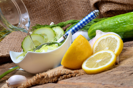 Close-up of pouring oil into Tzatziki - traditional Greek dressing or dip sauce, garlic, lemon, dill, cucumber, jug with oil, blue spoon and decoration in background