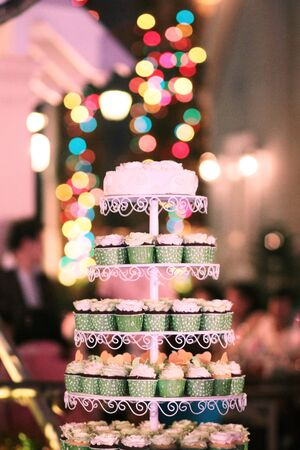 Foto für Wedding Cupcakes with colorful sprinkles in green cup with garland lights bokeh background - Lizenzfreies Bild