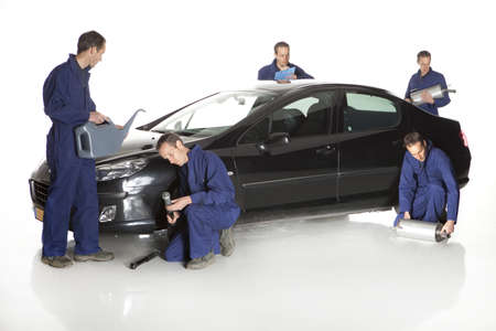 Portrait of confident worker with handful of mechanic stuff in front of car over white background