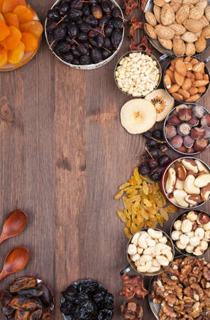 Frame of variety of fruits and nuts on a dark wooden surface