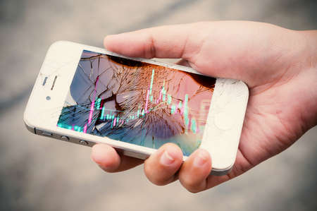 Photo pour Hands holding broken mobile smartphone with stock graph overlay. Investment risk stock concept. - image libre de droit