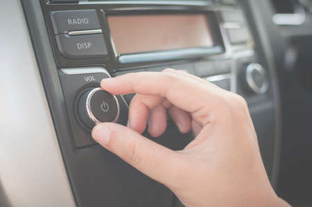 Photo for Hand tuning fm radio button in car panel. Retro image processed. - Royalty Free Image